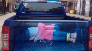 The image makes it appear there is a woman bound and gagged in the boot.