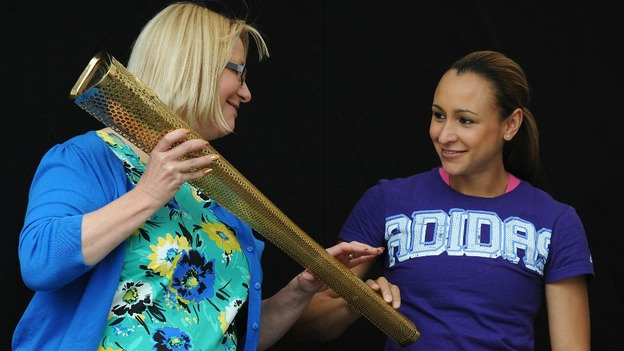 Jessica Ennis touches the Olympic Torch held by Tina English during a civic send-off event in Sheffield city centre