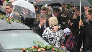 Mourners lay flowers on the hearse carrying the coffin of Cpl Michael John Thacker near RAF Brize Norton on June 7.