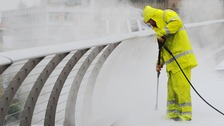 File photo of a worker using a high temperature pressure washer to remove chewing gum and clean the Millennium Bridge in London