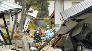 Rescue workers are seen between collapsed houses after an earthquake in Hakuba town, Nagano prefecture