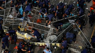 Riot officers demolish barricades.