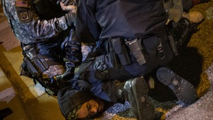 A policeman and member of the National Guard detain a man who was demanding justice for the killing of Michael Brown.