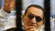 Hosni Mubarak waves to supporters inside a cage in a courtroom at the police academy in Cairo, April 2013.