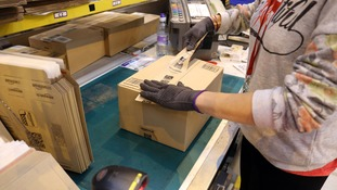 A worker packs an order at the Amazon UK Fulfilment Centre in Peterborough