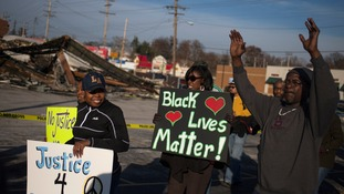 Supporters of the National Association for the Advancement of Coloured People (NAACP) stand outside the burned remains of a building in Ferguson.