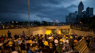 Pro-democracy protesters move a barricade at a demonstration site near the office of the Hong Kong Chief Executive.