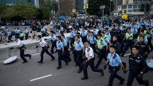 Massed ranks of police move towards the protesters.