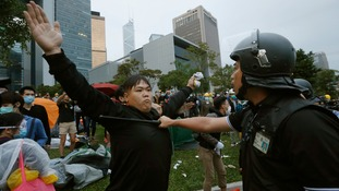 A protester refuses to budge as a policeman holds a baton to his chest.