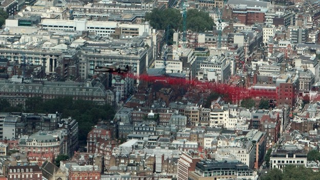 A Lancaster bomber drops poppies over Green Park in central London.