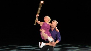 Jayne Torvill and Christopher Dean carry the Olympic Flame in the National Ice Centre