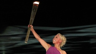 Jane Torvill carries the Olympic Torch during her ice dance routine with partner Christopher Dean