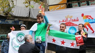 Ahmad Sobhe holds up a trophy as he celebrates winning a running race in Aleppo's Bustan al-Qasr neighbourhood, a rebel-controlled area.