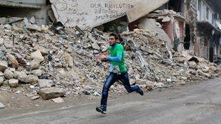 A participant runs past a damaged building as he competes in a running race along a street in Aleppo's Bustan al-Qasr