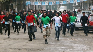 Participants compete in a running race along a street in Aleppo's Bustan al-Qasr neighbourhood, a rebel-controlled area.
