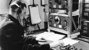 A radio dispatcher sending out messages in Morse Code to vehicles from the Information Room in the 1930s.