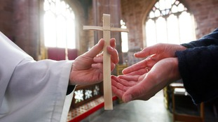 Palm crosses are distributed during Palm Sunday services.
