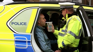 An actor demonstrates being breathalysed by police