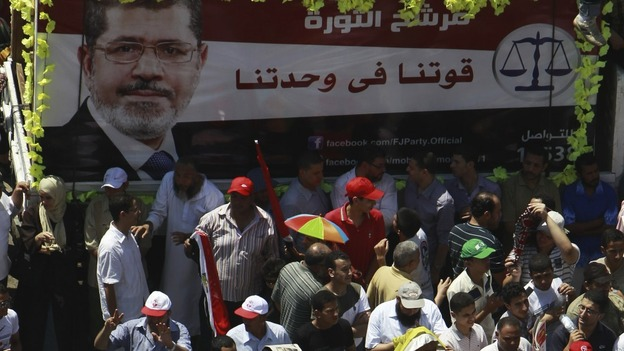 Supporters of Egyptian President-elect Mohamed Morsi shout anti-military council slogans at Tahrir square in Cairo