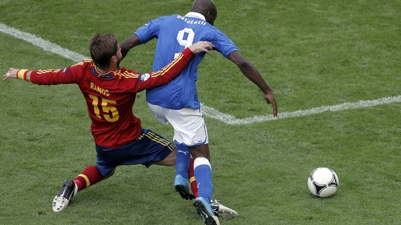 Spain defender Sergio Ramos tackles Mario Balotelli.