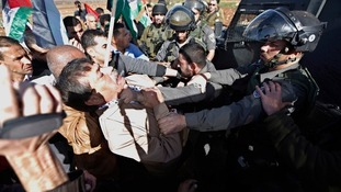 Ziad Abu Ein appears to be grabbed by an Israeli soldier during the protest.