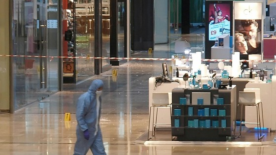 A forensics officer attends the scene at Westfield in Stratford, east London, after a man was stabbed to death