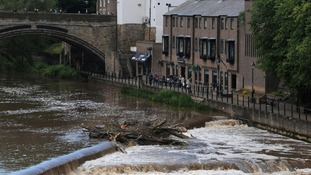 People look out over the fast flowing River Wear in Durham today after heavy rainfall in the area