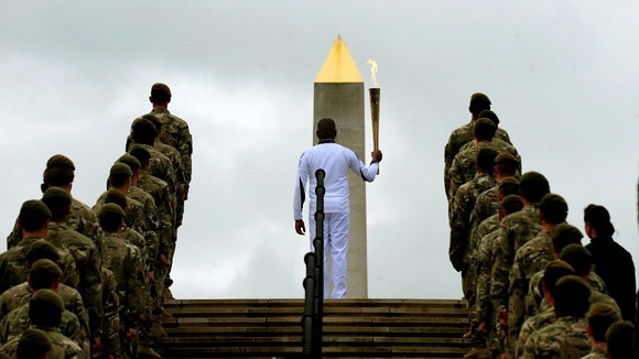 Corporal Johnson Beharry VC is flanked by soldiers as he carries the torch at the National Memorial Arboretum