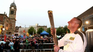 Torchbearer Leon Taylor carries the Olympic Flame on the Torch Relay leg through Derby City Centre.