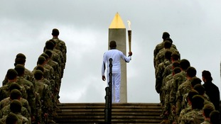 Lance Corporal Johnson Beharry VC is flanked by soldiers as he carries the torch at the National Memorial Arboretum