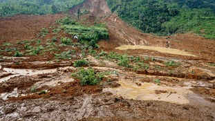 A house, center, is buried in the mud in a village that was swept away by a landslide .