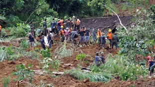 Rescue workers stand near houses buried in the mud after a landslide hit the village of Sampang in Banjarnegara December 13, 2014.