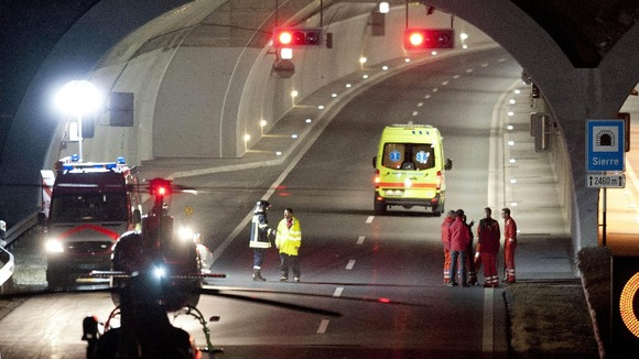 Rescuers work at the tunnel entrance after a bus crashed in the tunnel, in Sierre, Switzerland.