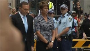 Prime Minister Tony Abbott and his wife stand in a moment of silence