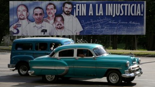 Cars drive past a billboard displaying the 'Cuban Five', with the slogan 'End the injustice'.