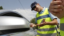 A French Gendarme distributes chemical breath testers which measure the level of alcohol in the breath