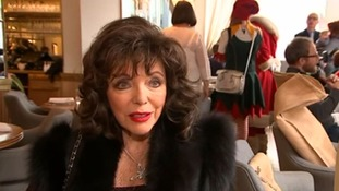 Joan Collins brings Christmas cheer to families at a charity breakfast.