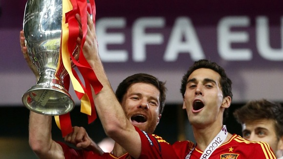 Spain midfielder Xabi Alonso lifts the trophy.
