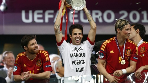 Spain midfielder Cesc Fabregas lifts a trophy wearing a t-shirt honouring the deaths of Spanish footballers and Manolo Preciado.