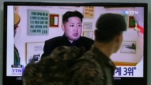 A South Korean soldier watches a TV news program showing North Korean leader Kim Jong Un.