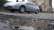 File photo dated 16/02/11 of a car passing a pothole, as local councils are to get a near £6 billion fund to fight potholes.