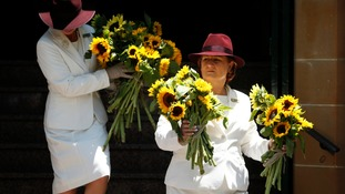Members of an all-woman funeral company bring sunflowers out of St Stephens Uniting Church in Sydney, December 23, 2014. following the funeral of Sydney cafe siege victim, cafe manager Tori Johnson.