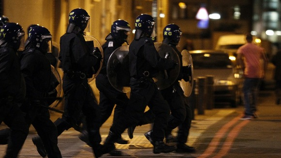 Police officers wearing riot gear run along a street in Tottenham, north London August 7, 2011.
