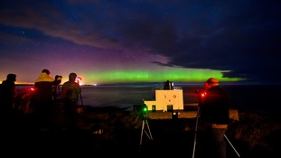 An Aurora is seen on the horizon behind Bamburgh Lighthouse in Northumberland.