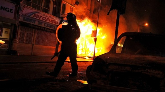 A riot policeman advances past a burning building in Croydon, south London August 8, 2011.