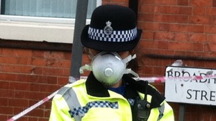 A police officer wearing a mask at the scene of the fire in Lenton in Nottingham