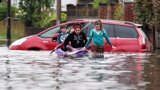Locals making their way in a boat along a flooded road in Felpham near Bognor Regis in West Sussex.