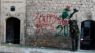 A Free Syrian Army fighter sprays graffiti on a wall prior to the new year in Aleppo