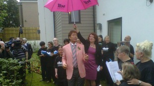 Sir Cliff Richard sings, as a willing volunteer shelters him with an umbrella.