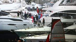 Visitors view luxury yachts at the Boat Show